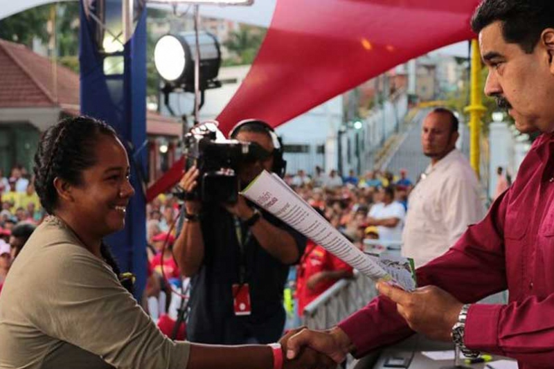 President Nicolas Maduro gives a collective land title to campesino leader Yendi Eraso Gonzalez